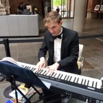 Live music being played on a keyboard by a dapper clad gentleman.